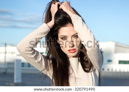 Attractive young brunette woman with pretty makeup shaking head, touching hair by her hands, standing outdoors on a bright sunny day in front of buildings under the blue sky - stock photo