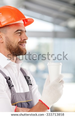 Attractive young builder is drinking coffee and resting. He is standing and holding a cup. The man is smiling with pleasure - stock photo