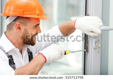 Attractive young builder is installing lock in door. He is holding a screwdriver and kneeling. The man is smiling. He is wearing a helmet - stock photo