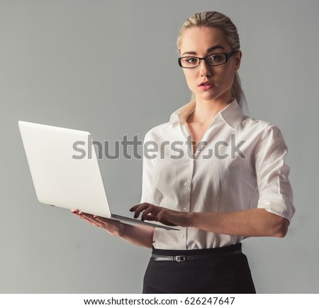 Attractive young business lady in suit is using a laptop and looking at camera, on gray background
