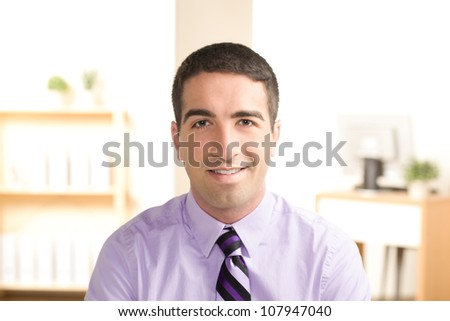Attractive young business man looking at camera with smile wearing a purple shirt and tie. - stock photo