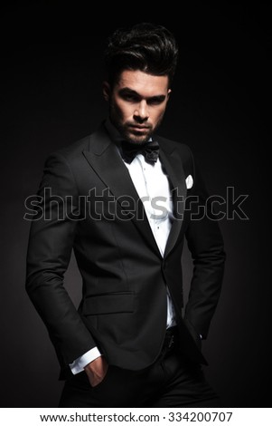 Attractive young business man looking at the camera while holding both hands in his pocket.