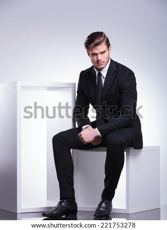 Attractive young business man looking at the camera while sitting on a white modern chair.