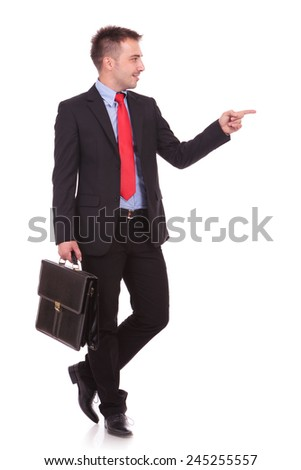 Attractive young business man pointing at something to his left while holding a black briefcase.