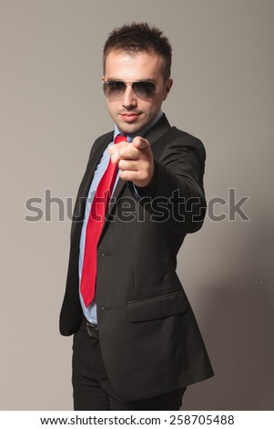 Attractive young business man pointing at the camera, on grey studio background. - stock photo