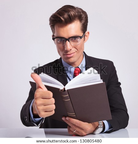 attractive young business man sitting at the desk with a book in his hand and showing thumbs up sign with the other while looking at the camera with a confident smile, on gray background - stock photo