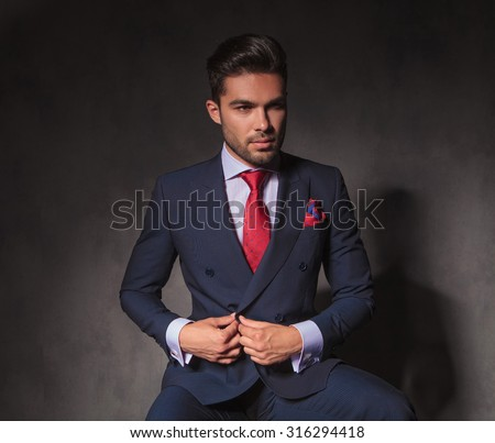 Attractive young business man unbuttoning his jacket while looking away from the camera.