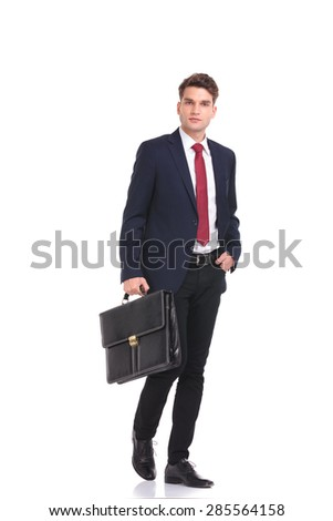 Attractive young business man walking with a briefcase in his hand. - stock photo