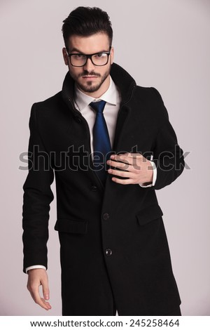 Attractive young business man wearing a long elegant coat looking at the camera while holding one hand on his coat. - stock photo