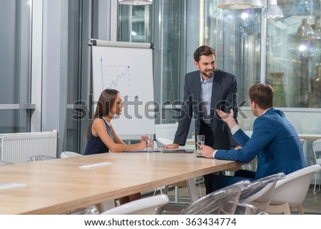 Attractive young business partners are discussing the plan of work. The man and woman are sitting at the table. Another businessman is standing and smiling - stock photo