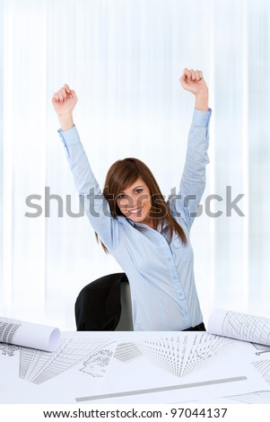 Attractive young business woman at desk raising hands for success.