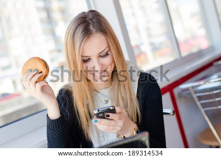 attractive young business woman eating a delicious burger in a cafe or restaurant having fun holding the mobile cell phone chatting and happy smiling closeup portrait - stock photo