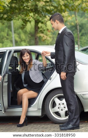 Attractive young business woman getting out of the car with gentleman holding her hand - stock photo