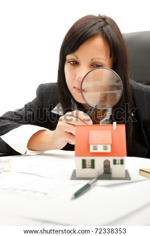 Attractive young business woman inspects a home with magnifying glass - stock photo