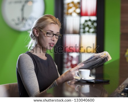 Attractive young business woman reading a newspaper - stock photo