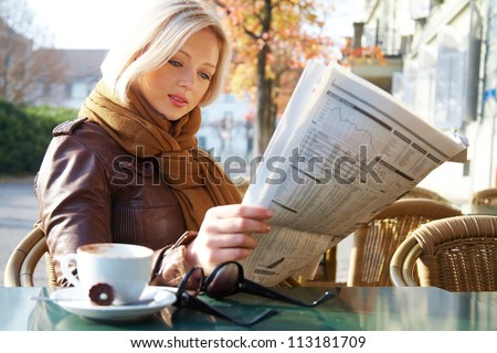 Attractive young business woman reading a newspaper at outdoor cafe