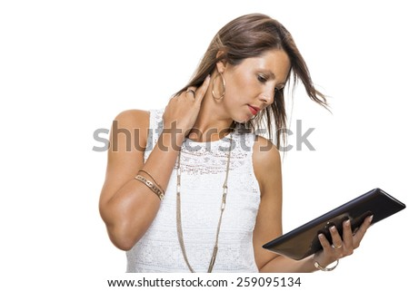 Attractive young business woman standing chatting on a mobile while simultaneously reading a tablet computer with a smile, isolated on white