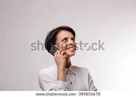 Attractive young business woman talks on her smartphone - stock photo