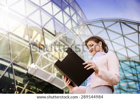 Attractive young business woman with clipboard in the city - stock photo