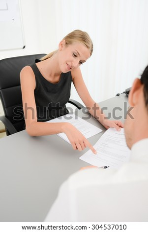 attractive young business woman with customer in office signing an agreement sales contract - stock photo