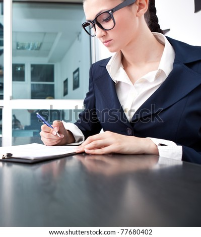 attractive young business woman writing a contract in office - stock photo
