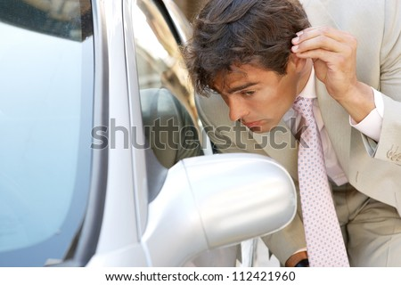 Attractive young businessman grooming using a car's reversing mirror to tidy his hair up, preparing for a business meeting. - stock photo
