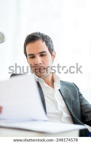 Attractive young businessman in a jacket sitting reading a report or document with a serious expression as he analyses the information with a white wall and copyspace behind him. - stock photo