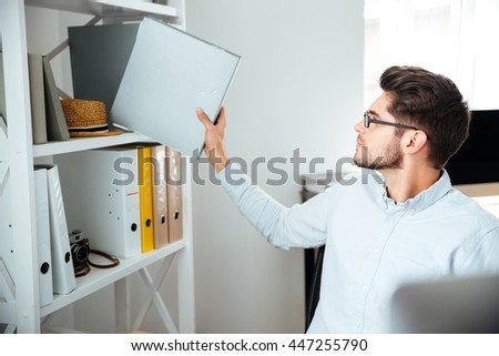 Attractive young businessman in glasses sitting and taking folder with documents in office - stock photo