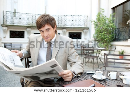 Attractive young businessman reading the newspaper while having a coffee and sitting at a coffee shop terrace in a classic office buildings city square.
