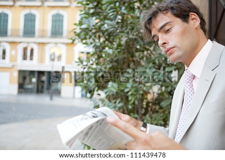 Attractive young businessman reading the newspaper while sitting in the city with classic office buildings around him. - stock photo