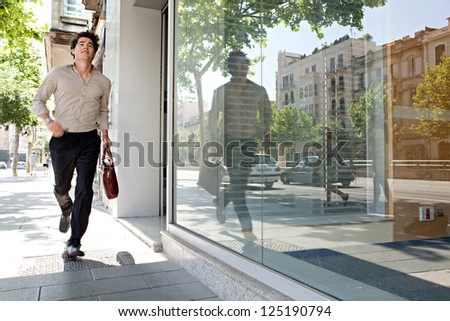 Attractive young businessman running though the city being late for work.