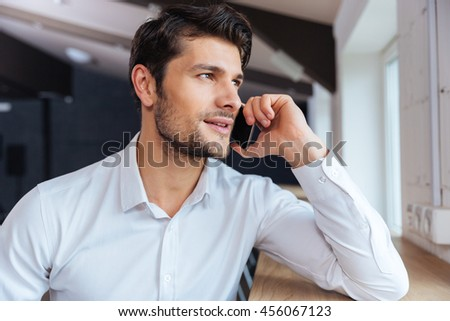Attractive young businessman sitting and talking on mobile phone sitting indoors in cafe