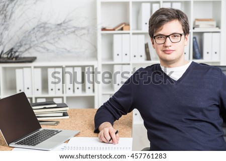 Attractive young businessman sitting at desk with blank laptop, smartphone and paperwork. Office interior in the background. Mock up