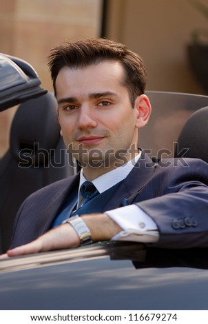 Attractive young businessman sitting in his posh cabrio