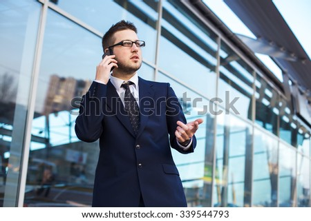 Attractive young businessman speak a cell phone, smiling. Standing  in front of a modern office building.