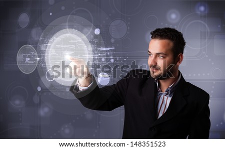 Attractive young businessman touching abstract high technology circular buttons
