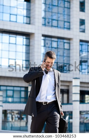 Attractive young businessman using a cell phone, smiling. Taken in front of a modern office building on a beautiful sunny day.