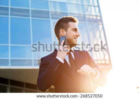 Attractive young businessman using a cell phone. Standing in front of a modern office building. - stock photo
