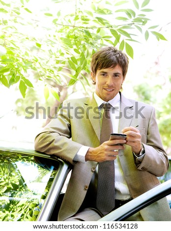 Attractive young businessman using a digital tablet while leaning on the door of his car in a classic city street. - stock photo