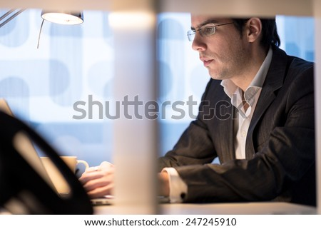 Attractive young businessman wearing glasses sitting working at his desk typing information into a laptop computer with a mug of coffee close at hand, side view. - stock photo