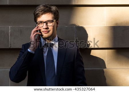 Attractive young businessman with glasses having mobile phone conversation outside on concrete tile background - stock photo