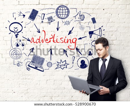 Attractive young businessman with laptop on white brick background with creative communication sketch. Digital advertising concept
