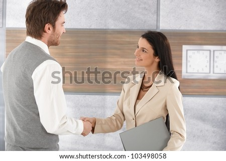 Attractive young businesspeople shaking hands in modern office, smiling. - stock photo