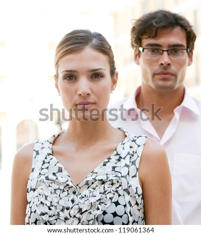 Attractive young businesswoman and businessman standing together in front of classic office buildings in the city. - stock photo