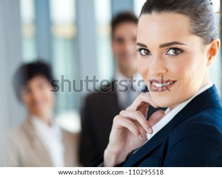 attractive young businesswoman closeup portrait with co-workers in background - stock photo