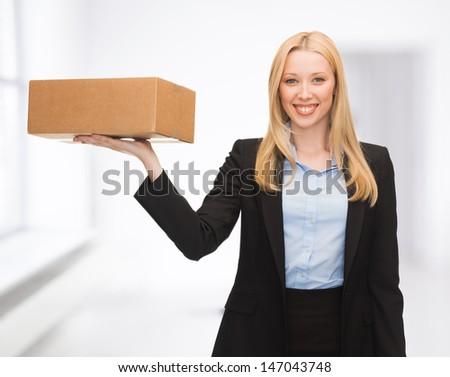 attractive young businesswoman delivering cardboard box indoor - stock photo