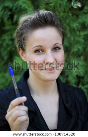 Attractive Young Businesswoman Holding a Pen Smiling - stock photo