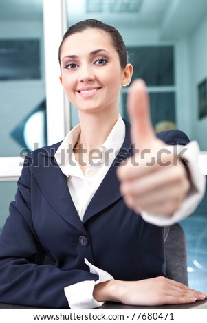 attractive young businesswoman holds out her hand in a thumbs up gesture - stock photo