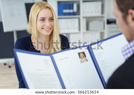 Attractive young businesswoman in a job interview with a corporate personnel manager who is reading her CV in a blue folder, over the shoulder focus to the young applicant - stock photo