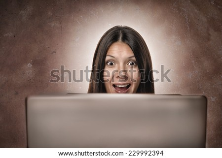 Attractive young businesswoman looking in amazement and delighted surprise at the camera from behind her computer monitor isolated on white - stock photo